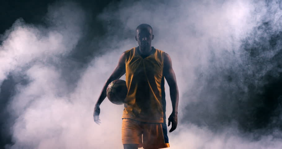 Determined sportsman walking with basketball in basketball court 4k