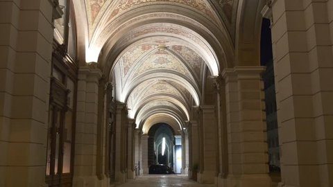 Archway with fresco on ceiling, historical building with illuminated arch corridor and columns at night