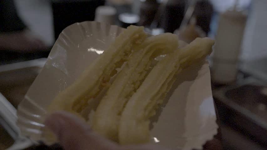 Slow-motion. Sprinkle some sugar on churros. SLOG3, medium shot.
