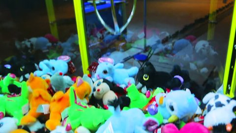 Catching toys in the street grabbing machine. Claw machine full of toys