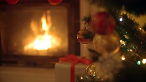 Closeup image of golden and red baubles on Christmas tree. Burning fireplace on the background.