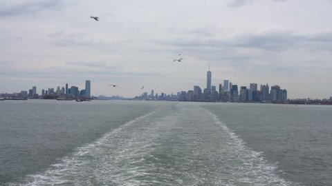 View of Manhattan from the Staten Island Ferry, with waves in the wake of the ferry across New York Harbor