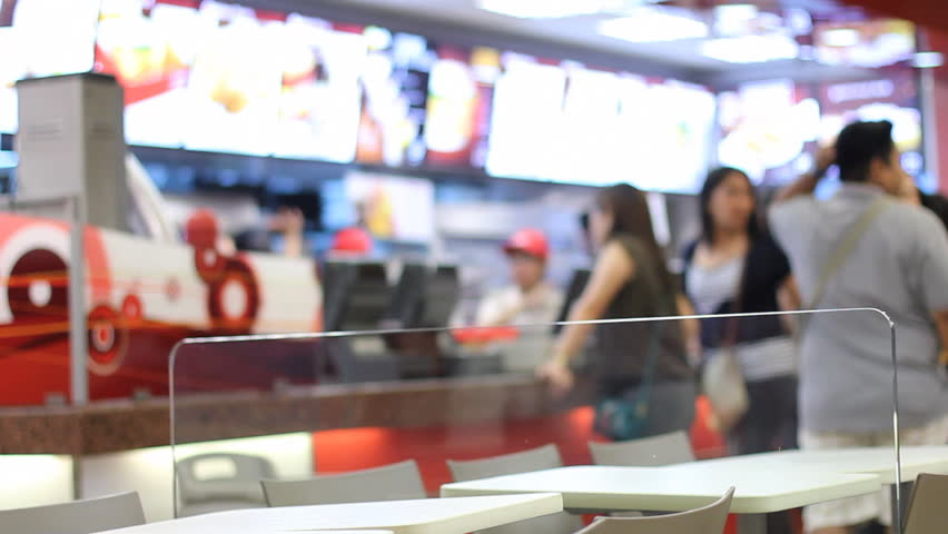 People lining up in a fast food store. Defocused background.