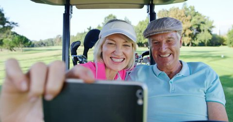 Two golfers taking a selfie in golf buggy at golf course