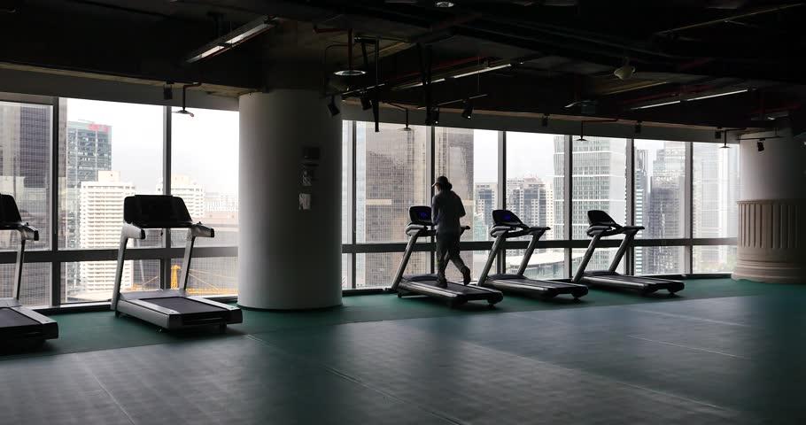 4k,male running on cardio treadmills,urban business building,overpass traffic from window. gh2_11618_4k