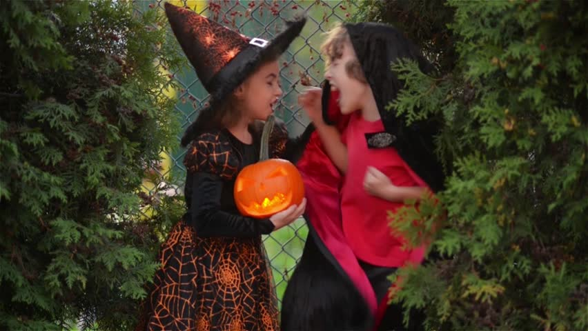 Children wearing witch costumes with hats playing with pumpkin with a burning candle in autumn Park on Halloween. boy and girl scare each other. Kids trick or treat.