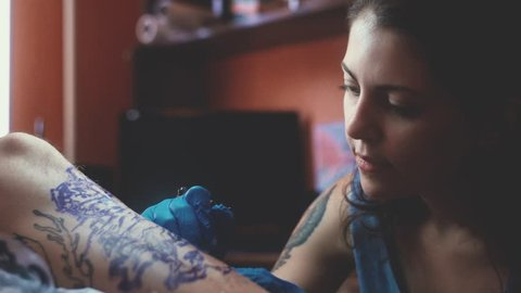 The tattoo artist at work. A girl holding a tattoo machine and applied in a pattern on the skin. Blue ink in the tattoo machine. The girl - the master of tattoos. Abstract pattern tattoo.