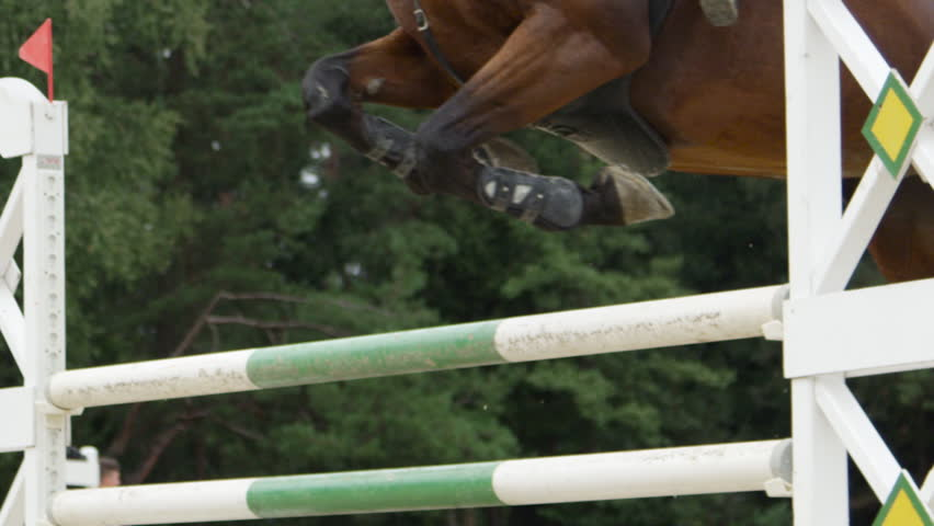 SLOW MOTION, CLOSE UP: Brown horse jumping over vertical fence and performing in competitive jumping event in outdoors sandy parkour riding arena. Unrecognizable person riding powerful gelding