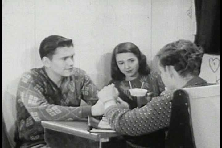 A shy boy makes eye contact with a girl he'd like to take to a school dance in 1947. (1940s)