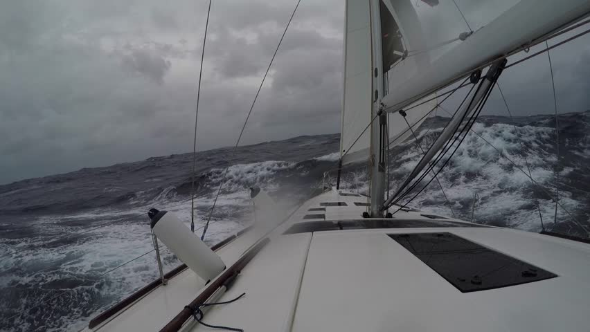 Sailboat moving through storm. Big waves and strong wind. Strong pitching and roll.