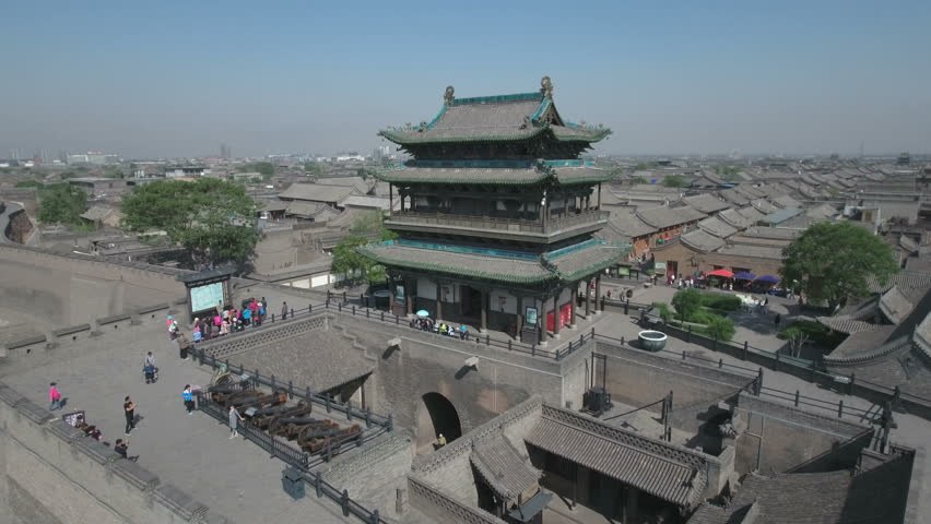 Reverse flyaway from a beautiful renovated pagoda building (serving as the entrance to the walled city of Pingyao), reveals a stunning panoramic overview of the town, in central China