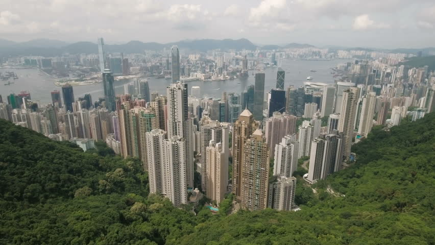 HONG KONG - JULY 2016: Aerial drone view of the beautiful high-rise commercial and residential buildings of Hong Kong island and Kowloon. Flying from the Victoria Peak towards the skyline of the city.