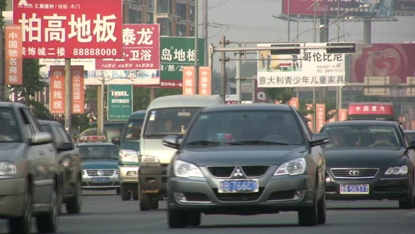 QINGDAO - 3 MAY 2010: Traffic drives past advertising billboard reading Chinese characters in Qingdao, China