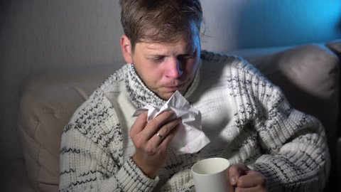 funny Sick man blowing his nose in the tissue, young ill man in bed holding tissue cleaning snotty nose having temperature feeling bad infected by winter grippe virus