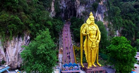Amazing close view of the Murugan statue and many stairs of entrance to the Batu Caves, a limestone hill that has a series of caves and cave temples in Gombak