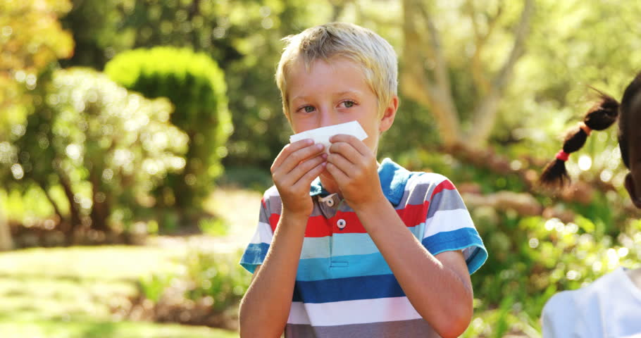 Kids blowing their nose with handkerchief while sneezing in park on a sunny day 4k