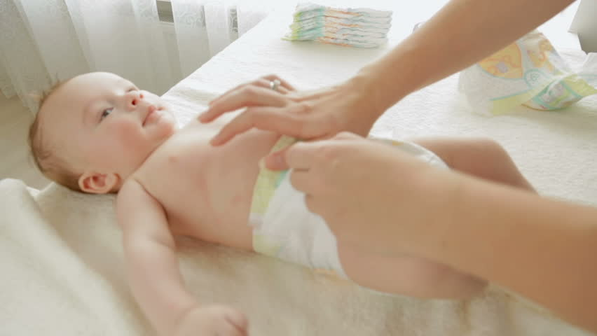 Closeup shot of young mother changing diapers to her 3 months old baby boy lying on table