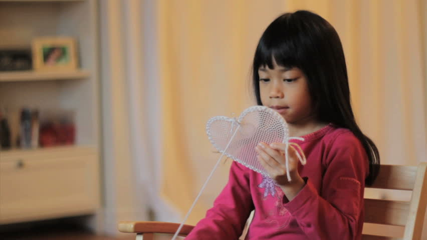A cute little 5 year old Asian girl creates a beautiful heart shaped gift out of stitching just in time for Valentine's Day.
