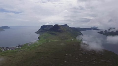 Aerial shot of the Faroe Islands with mountains and clouds