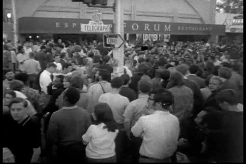 At an open mic protest on Berkeley Campus, a Persian man inspires students to fight the man in 1968. A guitarist sings and performs. (1960s)
