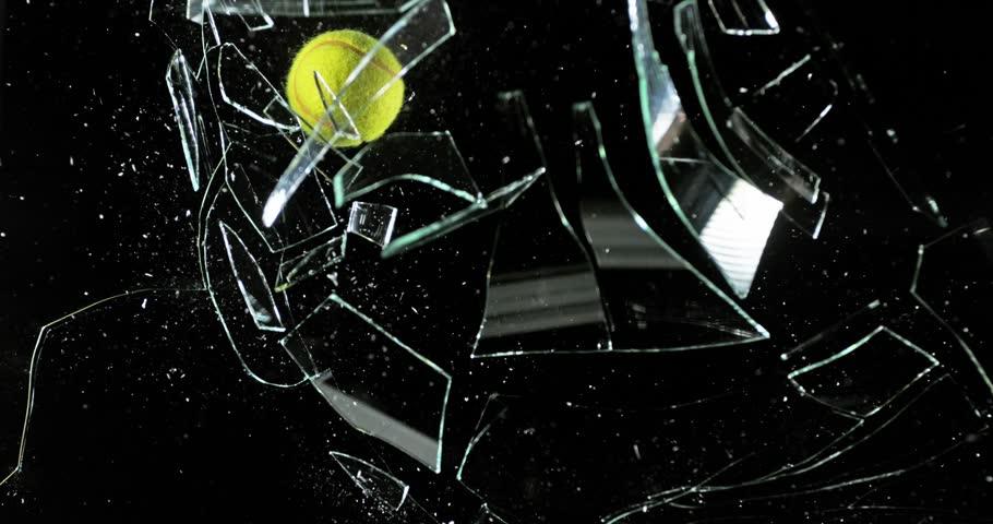 Tennis Ball breaking Pane of Glass against Black Background, Slow Motion 4K