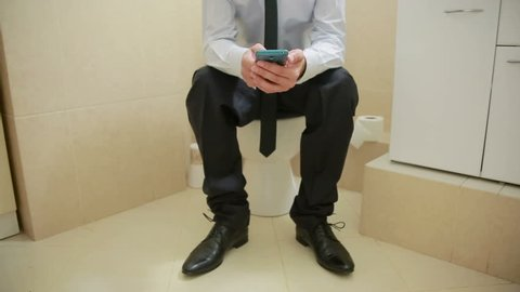 Male businessman watches the news on the phone sitting on the toilet