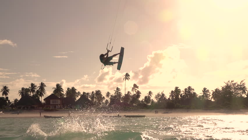SLOW MOTION: Happy smiling kite surfer kiteboard jumping in turquoise ocean at golden sunset. Cheerful kiteboarder kiting and jumping in blue lagoon of tropical island Zanzibar in summer evening