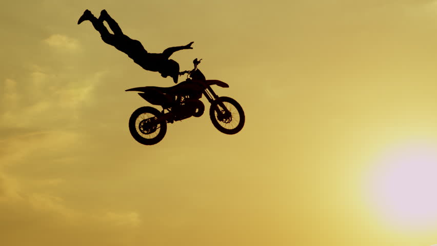 SLOW MOTION SILHOUETTE: Pro motocross rider riding fmx motorbike, jumping big air kicker performing extreme stunt. Professional biker jumps no hander trick over golden sunset sky above trees