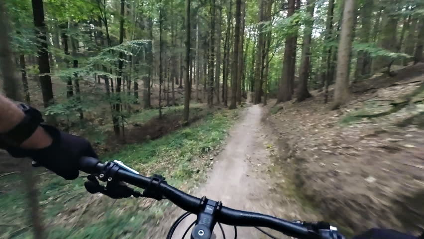SLOW MOTION: Jumping and riding on enduro mountain bike in autumn forest. Downhill ride in woods. View from first person perspective POV.