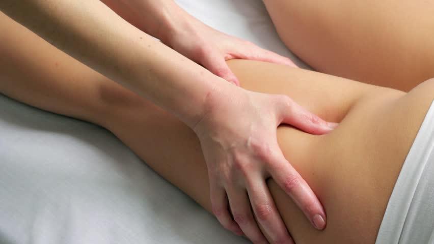 Close up locked down shot of chiropractor massaging female hamstrings on leg.Originating camera: Canon 7d mark11. Shutter speed 1/50. Aperture f5,6. Recording format H.264