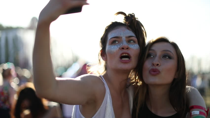 Female friends taking selfie at summer festival