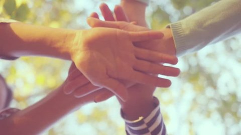 Many hands together over sky and trees in slowmotion. 1920x1080