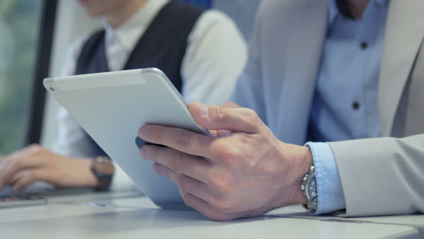 Male business commuter using an app on his tablet on the train. Young professional working on a device while traveling to a job. | Shutterstock HD Video #20129572