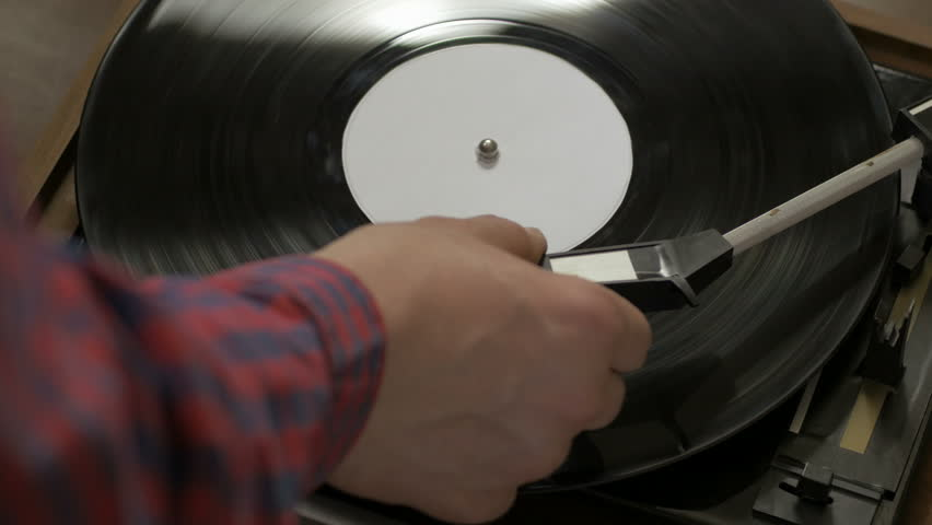 Close-up shot of a vinyl record spinning on a turntable. Man wearing shirt putting a needle on a black disc. | Shutterstock HD Video #20131420