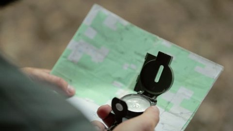 Over the shoulder of a man uses a magnetic navigational compass and map. Shallow focus.