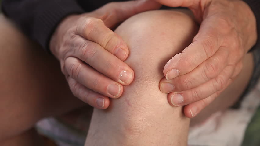 man tries to ease the pain in his knee