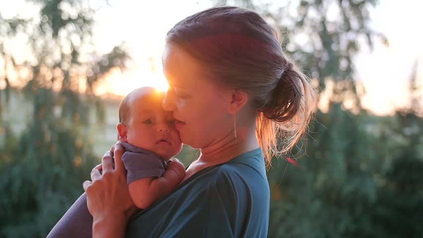 Happy young woman raising her little baby in the evening park. Handheld shot | Shutterstock HD Video #20136670