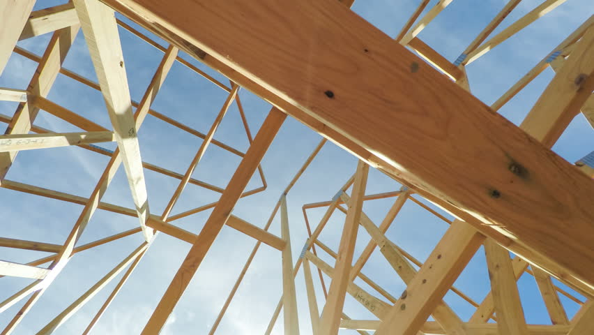 Roof beams of a modern American home in mid construction phase, looking up toward blue sky with sunlight