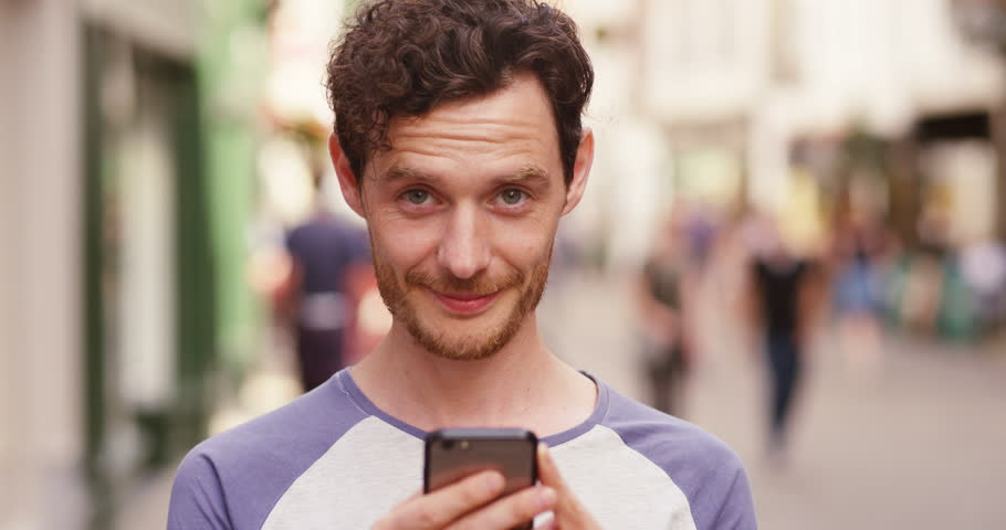 4k, Close up portrait of handsome young man using cellphone outdoors in the city. Slow motion.