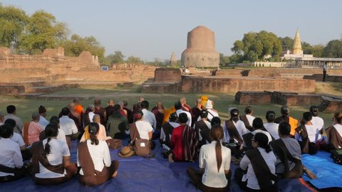 Sarnath,India - February 25,2016: Pilgrims praying in towards Dhamekh Stupa