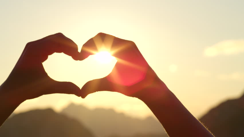 SLOW MOTION, CLOSE UP: Unrecognizable woman catching setting sun with her heart shaped fingers. Young girl making the symbol of love with her hands against stunning golden sky and rising morning sun #20240860
