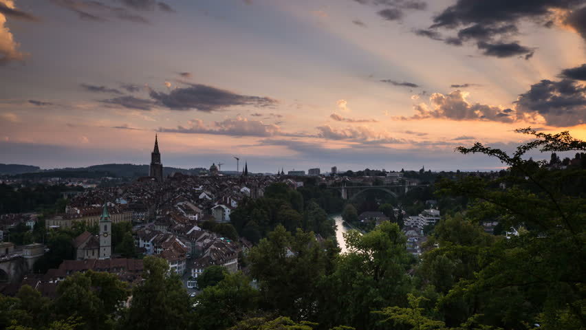 Bern, Switzerland day to night timelapse Colorful sky and clouds after sunset, while the city lights start to turn on over the rooftops of historic old town of Bern.