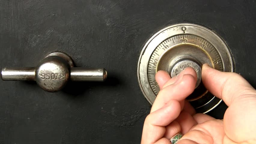 Close up of mans bare hands unlocking combination to large antique safe (circa 1906).   View from straight on