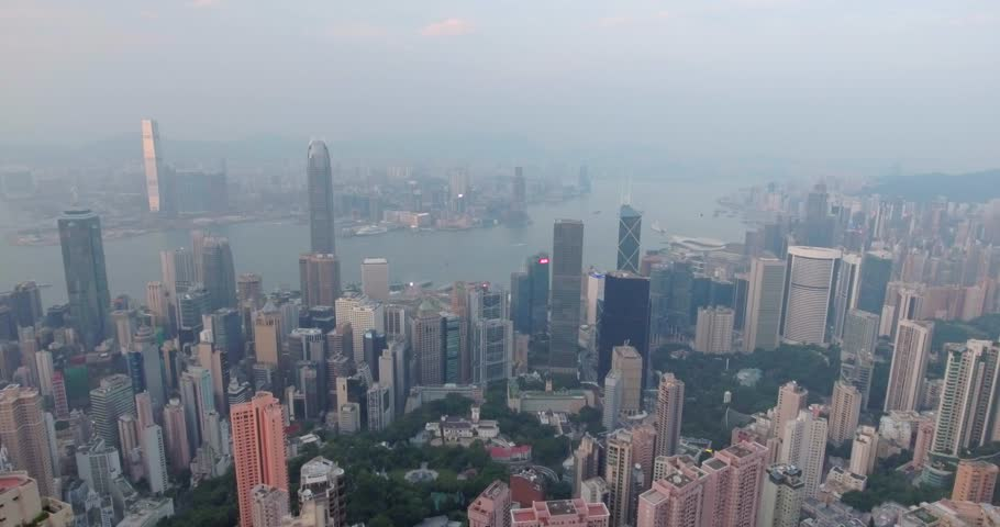 Beautiful aerial shot of many high  skyscrapers covered with sunset fog or haze in Hong Kong, China. Top view of Victoria Harbour from Victoria Peak at sunset. City skyline. | Shutterstock HD Video #20275000