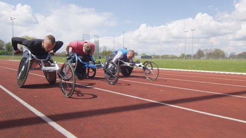 4K Disabled wheelchair athletics team competing in a race at race track. Shot on RED Epic.