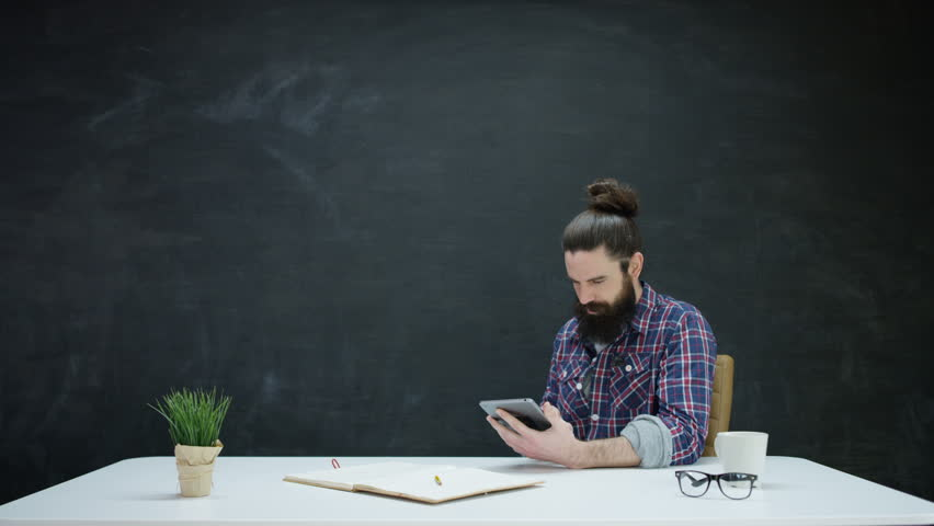 4k pensive hipster man with computer tablet on blank chalkboard 4k hipster man working on tablet computer looking for inspiration on blank chalkboard behind him voltagebd Image collections