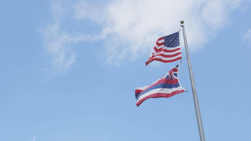 Hawaii State flag and American flag of USA waving on blue hawaiian sky.