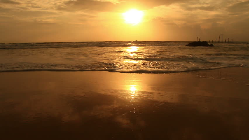 Sunset on the beach - Tranquil idyllic scene of a golden sunset over the sea, waves slowly splashing on the sand | Shutterstock HD Video #20299060