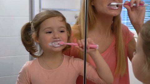 Young attractive mom and her cute daughter brush their teeth in front of the mirror.
