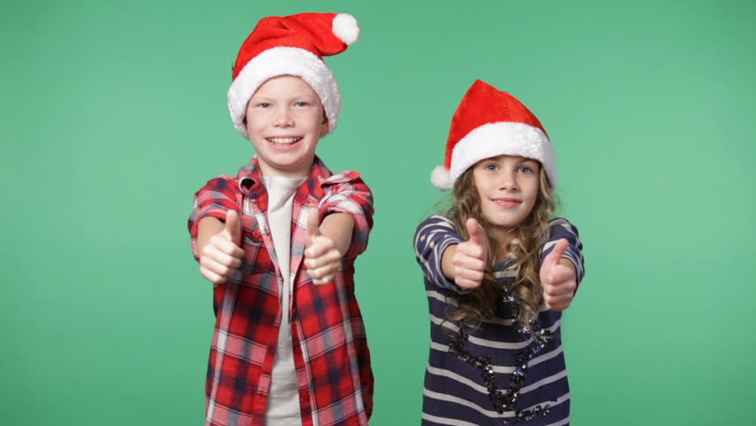 Little girl and boy in christmas caps showing thumbs up and smiling, chroma key green screen background | Shutterstock HD Video #20323600